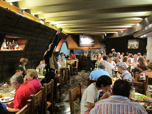 Look at the server on the left pouring the sidra from above his head.